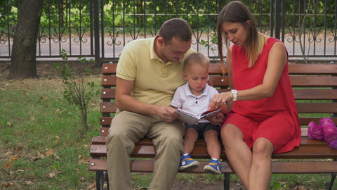 Young parents show a young son a book Footage