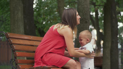 A little boy runs up to his mother sitting on a bench Live Action