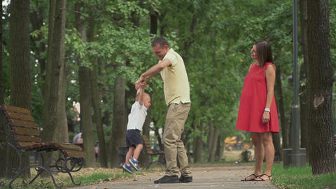 Dad circles his little son in a circle n the park Live Action