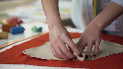 Stylist transferring template on textile pattern, process of clothes creation Live Action