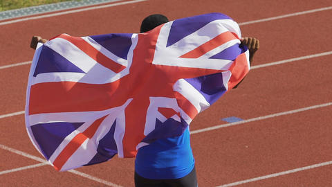 Excited champion showing flag of Great Britain to supporters, pride of nation Live Action