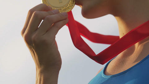 Happy sportswoman kissing gold medal and smiling, female winner rejoice victory Live Action