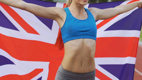 Smiling gymnast celebrating victory and holding flag of Great Britain, pride Live Action