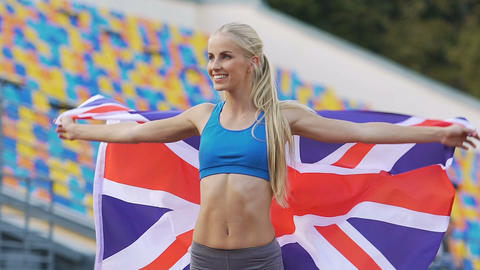 Blond athlete holding flag of Great Britain and rejoicing victory in competition Footage