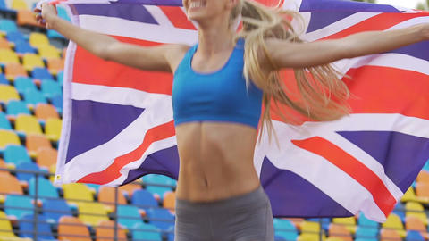 Pretty female runner winning competition, athlete holding flag of Great Britain Live Action