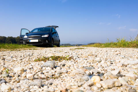 Black van parked on gravel road, low angle, copyspace Photo