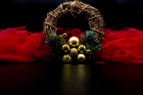 Twig Christmas wreath with golden decorations and red fabric on Photo