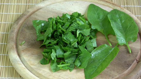 Rotating fresh healthy chopped cutted spinach leaves on wooden chopping board Live Action