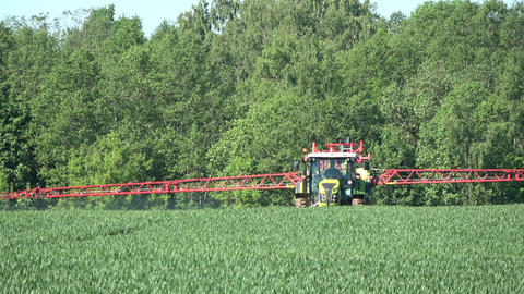 Panevezys district, Lithuania – May 2017: Agriculture tractor spraying crop field in summer time Live Action