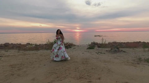 Beautiful girl in a long evening dress walks by the river. Shot on drone Footage