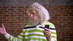 Cool caucasian senior man with great white curly hair and nice beard is having Footage