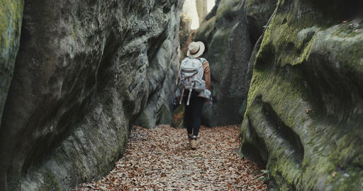 Back view of young traveler girl walking at rocks, woman... Stock Video Footage