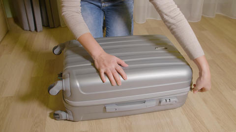 Girl closing zipper fastener on travel suitcase. Woman pulling zipper suitcase Footage