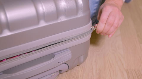 Close up female hand closing zipper fastener on travel suitcase on wooden floor Footage
