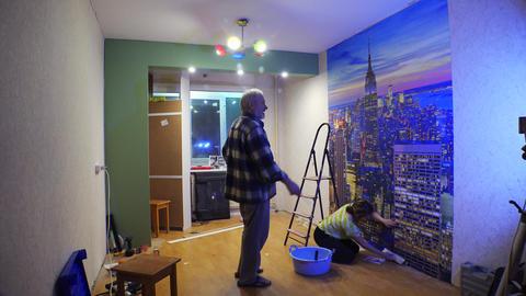 Family photo wallpaper paste. Renovated apartment. 4K Footage