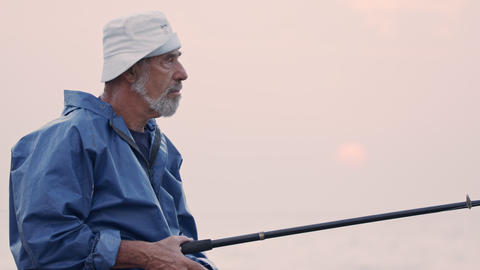 Old fisherman standing on sea side rocks and fishing against the sunset Footage