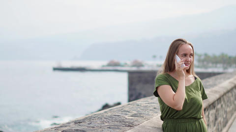 Beautiful girl in a green dress talking on the phone standing on the waterfront Footage
