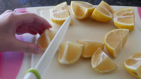 Motion of woman using ceramic chef knife and cutting lemon on cutting board with Live Action
