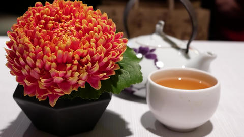 Motion of hot tea and flower on table and blur motion of people enjoy meal Footage