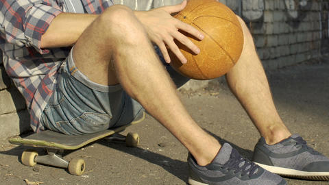Teenage boy in casual clothing sitting on skateboard, active leisure time Footage