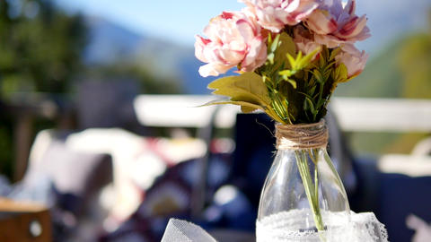 Wedding bouquet of flowers in a bottle decorates the dining table on the porch Live Action