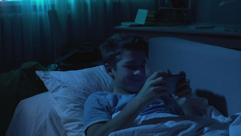Male student playing games on smartphone in bed at night, gadget addiction Live Action