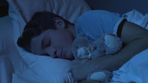 Closeup of sleeping teenage boy hugging his white teddy-bear toy, healthy sleep Live Action