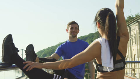 Young athletic couple stretching together outdoors before morning run Footage