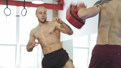 Handsome bearded muay thai fighter training with his coach at the gym Live Action