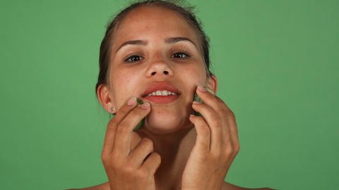 Gorgeous woman massaging her face with slices of cucumber ビデオ