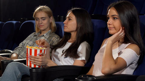 Young woman annoyed by her friends eating her popcorn at the cinema Footage