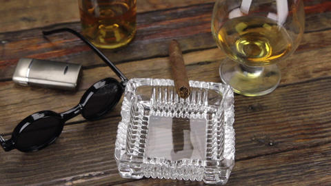 Luxurious cigar, glass of alcohol and stylish sunglasses on a vintage wooden Footage