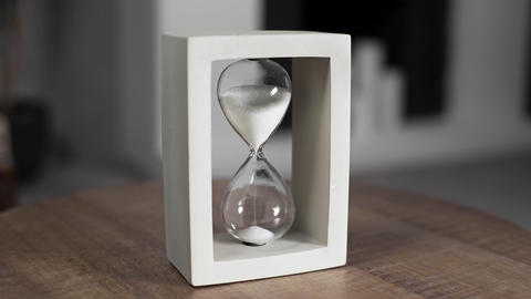 Hourglass with white sand is measuring time, sand in the sandglass, hourglass is Live Action
