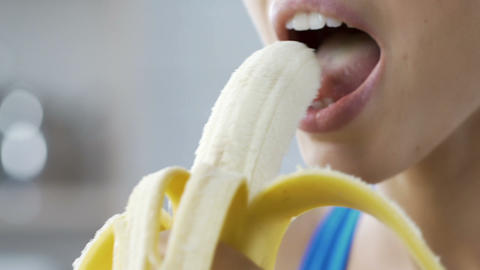Young lady eating banana and smiling, quick and healthy snack on break, calories Live Action