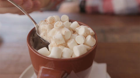 cocoa with marshmallows.man takes a spoon of cocoa with marshmallows Footage