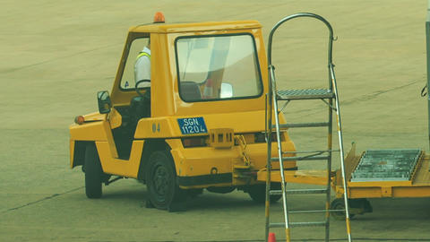 Airport Worker Clings Bulk Cargo Loader to Truck on Airfield Footage