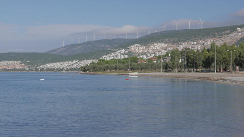 Wind farm on the top of the mountains surrounded by clouds with sea and a resort ビデオ