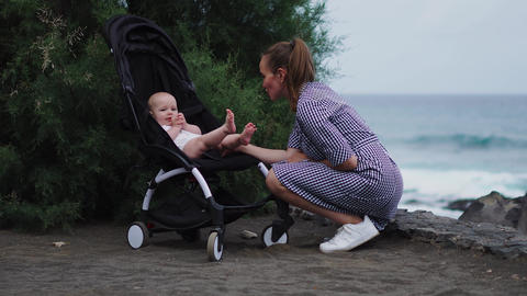 side view of young mother pushing baby stroller over summer beach background Live Action