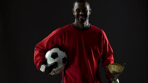 Excited black football winner holding prize and ball, sport reward, happiness Live Action