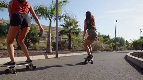 Two girls on skateboards in short shorts rides along the road along the beach Live Action