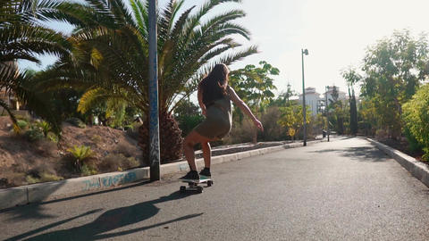 Girl on a skateboard in short shorts rides on the road along the beach and palm Live Action