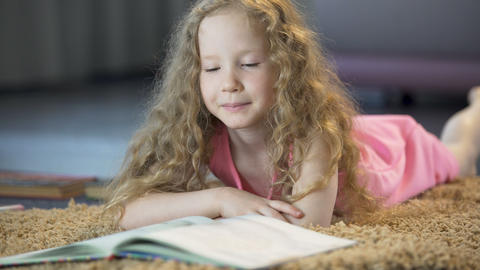 Smart young girl turning book pages, reading interesting literature, education Footage