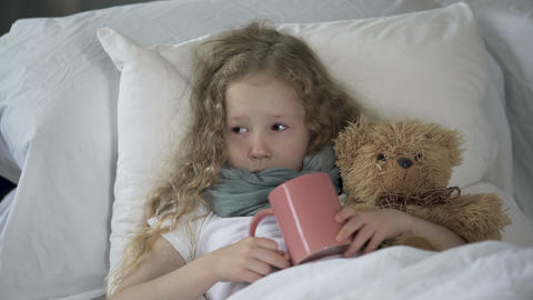 Sick child lying in bed with hot drink in mug, ill girl crying from throat pain Footage