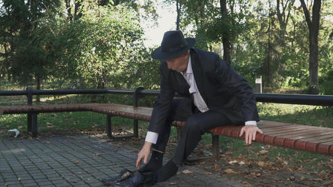 Drunk old man takes off his shoes and lies down on the bench Live Action