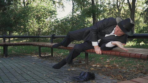 Drunk man lays comfortable at bench in the park Footage