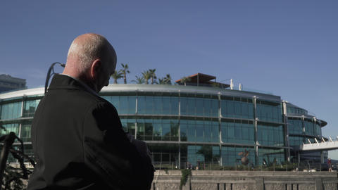 Old man in a strict coat against the background of a modern building Live Action