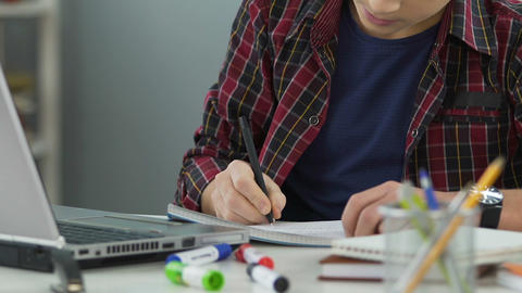 School boy accurately doing his homework, writing exercise in notebook, close up Live Action