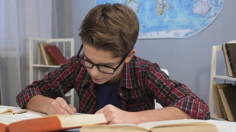 Genius boy in glasses doing homework task, writing answers in notebook, essay Live Action