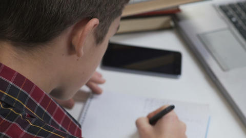 Pupil thinking over difficult homework, writing exercise in notebook, back view Live Action