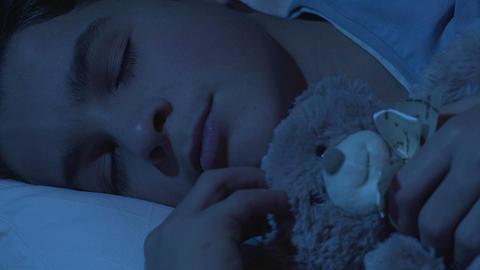 Sweet healthy dream of school boy cuddling teddy bear, comfortable mattress Footage